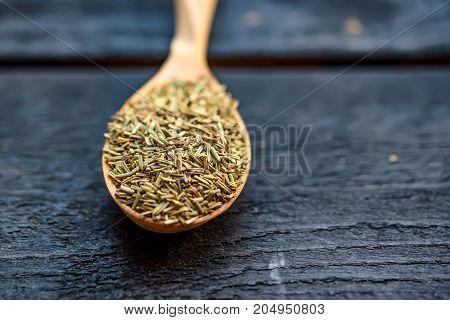 Close up image of wooden spoon filled with dried rosemary spice on dark wooden background