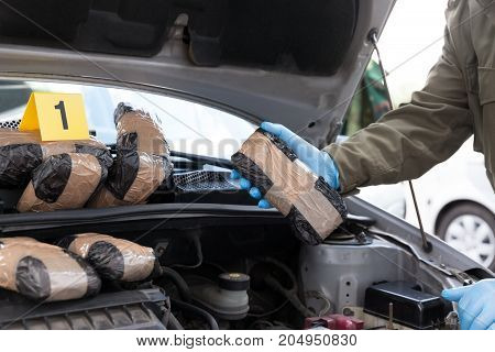 Hidden drugs in a vehicle engine compartment