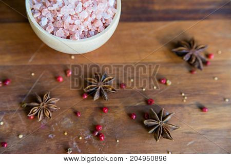 Pink Himalayan salt in a white bowl on wooden surface covered with anise and red peppercorn