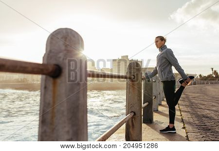 Woman Runner Doing Stretching At Seaside Promenade