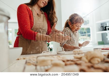 Mother and daughter kneading dough for making Christmas cookies. Little girl is excited in helping her mother in making cookies.