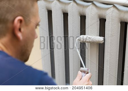 painter paints the cast iron radiator in gray color
