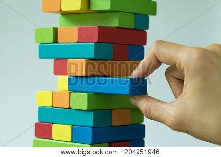Risk or stability concept with hand pulling colorful wooden block from the tower.