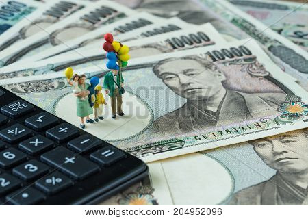 miniature figure happy family holding balloons standing on pile of japanese yen banknotes as financial safe haven or tax concept.