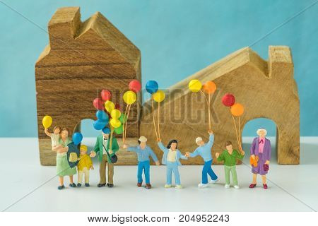 Miniature people with happy family holding balloons in front of wooden house as real estate or mortgage concept.