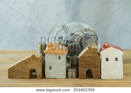 miniature house with stack of coins and coins in glass jar as financial saving investment or mortgage concept.