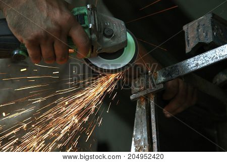 Metal works. Electric wheel grinding on steel structure in factory
