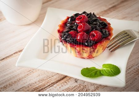 Fresh berry tartlet or cake filled with custard raspberry blueberry redcurrant and blackberry delicious dessert easy diet. Close up