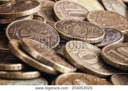 Background from coins of 10 rubles of bank of Russia. Small depth of sharpness. Horizontal format. Indoors. Without people. Color. Photo.