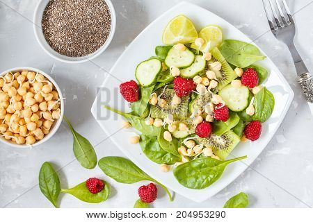 Green detox salad with spinach and berries. Diet and vitamin food concept top view.