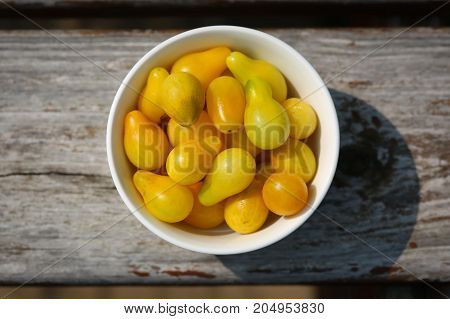 Heirloom yellow pear tomatoes in a small white bowl.