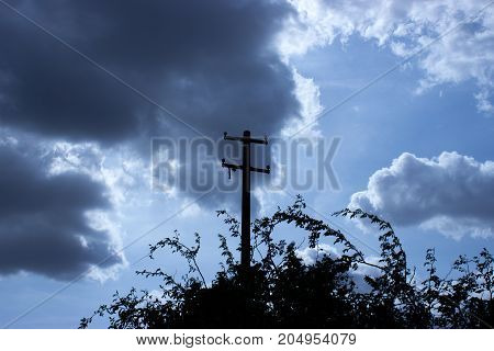 Electricity pole and despite dark clouds blue sky and sun shines.