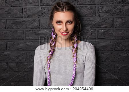 Portrait of model with colorful braids and makeup posing and smiling at camera on black background.
