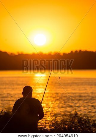 Fisherman with a fishing rod at sunset .