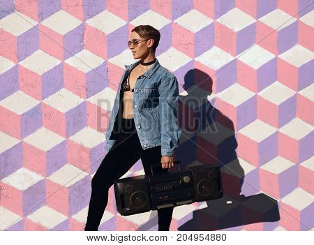 Young provocative girl in sunglasses and denim holding black boombox and looking away.