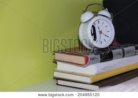analogue alarm clock on a stack of book - close-up