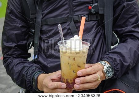 An Asian Man Holding A Cup Of Coffee