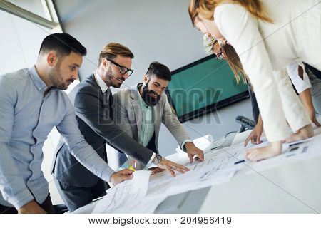 Picture of young architects discussing together about project