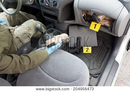 Drug smuggling. Police officer holding drug packages found in secret compartment of the car.
