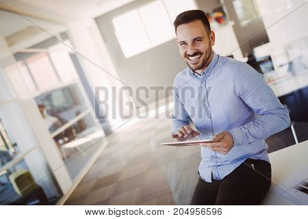 Portrait of handsome successful smiling architect holding tablet