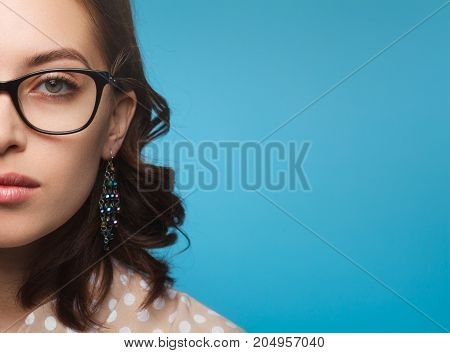 Crop view of woman in earrings and glasses posing on blue background.