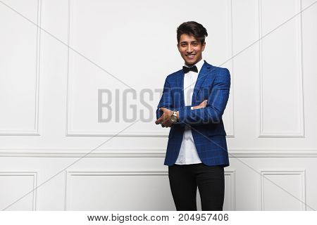 Handsome brunette guy wearing white shirt bow tie blue jacket holding arms crossed smiling standing.