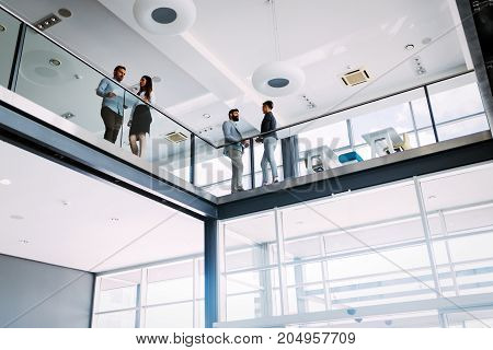Group of architects having discussion in hall of their company