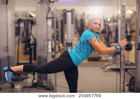 Bodybuilding. Strong Fit Woman Exercising In A Gym Machine - Leg Day