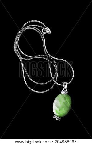 Vintage green nephrite pendant with diamonds on a chain isolated over black