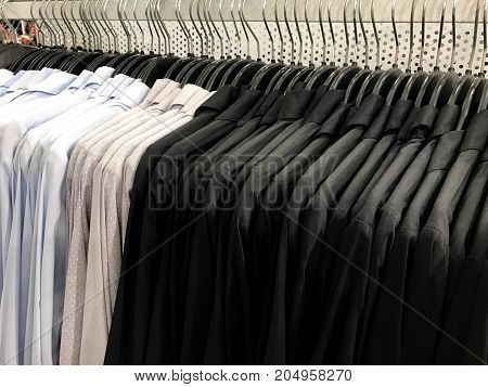 Blue gray with white dot and black shirt on hangers and rack in shopping store
