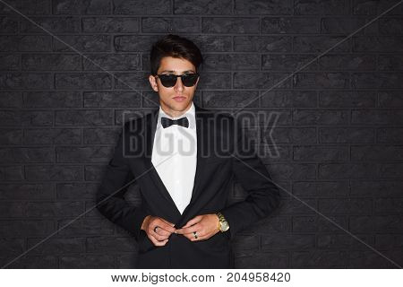 Handsome man in black formal suit and sunglasses posing on black background.