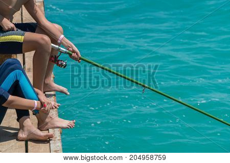 Children Are Fishing On The Pier. Close-up Of Hands And Rods
