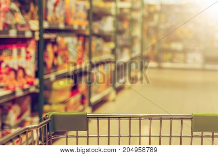 View From Shopping Trolley Into Abstract Blurred Supermarket Aisle Background. Vintage Tone