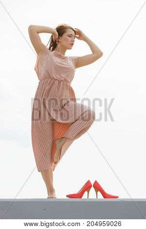 Hobby idyllic aspects of femininity concept. Woman dancing on jetty without shoes wearing beautiful long light pink dress.