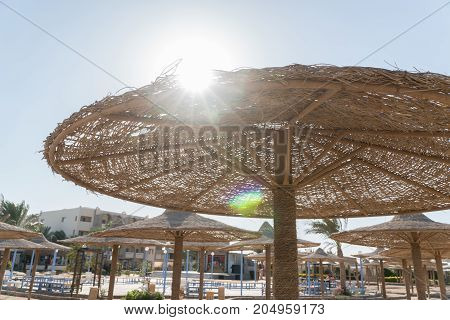View of the sun from under the umbrella. Wicker beach umbrellas in the background.