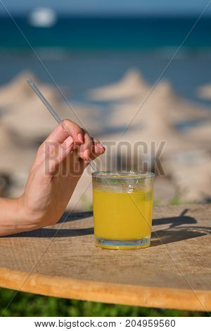 A woman's hand holds a straw. Glass of fresh orange juice against the sea.