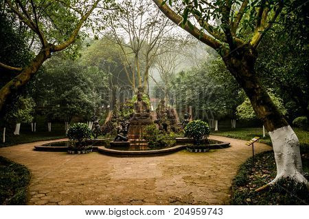 View of the fountain with statues in the park on the background of trees. Ancient fountain in Chinese style. LeShan, Asia