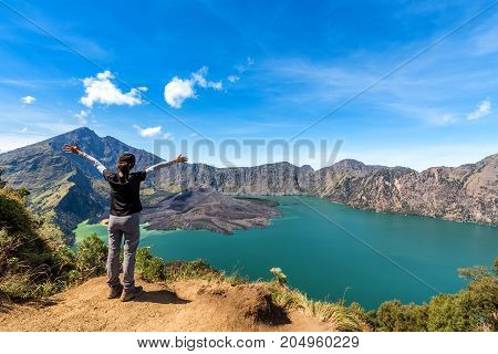 Woman spreading hand enjoy and happy with active volcano Baru Jari Lake Segara Anak and summit of Rinjani mountain view after finished climbing at Rinjani mountain Lombok Indonesia.
