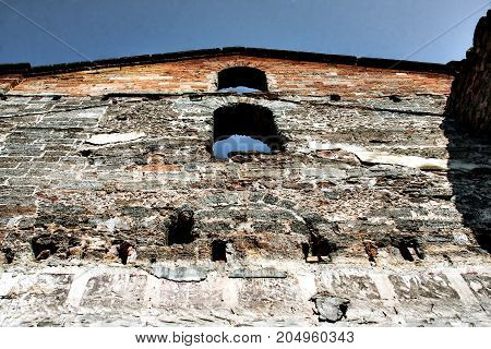 Old ruined castle made of bricks of different composition.
