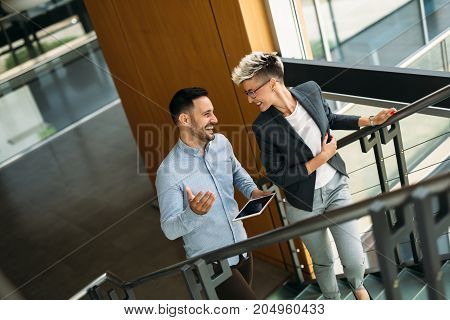 Picture of successful businessman and businesswoman having discussion in their company