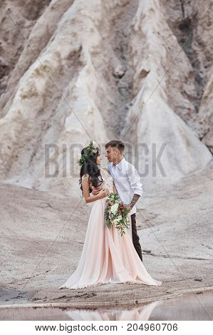 Woman With A Bouquet Of Flowers In The Arms Of Men. The Bride And Groom With Mountains In The Backgr