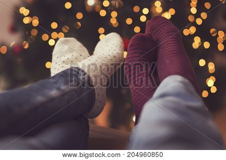 Detail of male and female feet wearing warm winter socks placed on the table with nicely decorated Christmas tree and Christmas lights in the background. Selective focus