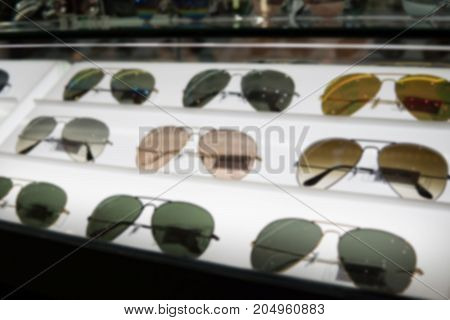 Blurry Background of the Shelves of brandname sunglasses, Sold in department store.