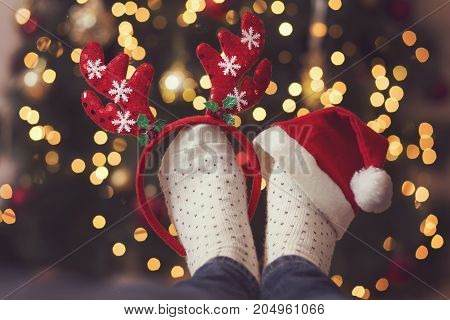 Detail of woman's feet wearing warm winter socks antlers and Santa's hat placed on the table with Christmas tree and Christmas lights in the background. Selective focus on the antlers