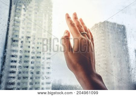 Loneliness On City, Woman Hand Touch Window With A Rain Drops On City Background.sun Rays. Find A So