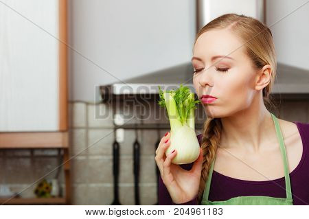 Woman In Kitchen Holds Raw Fennel Bulb Vegetable