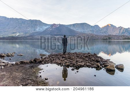 Young man standing and enjoy to see active volcano Baru Jari Lake Segara Anak. Rinjani mountain Lombok island Indonesia.