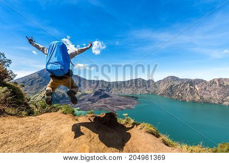 Hiker man with backpack spreading hand jumping and happy with active volcano Baru Jari Lake Segara Anak and summit of Rinjani mountain view after finished climbing at Rinjani mountain Lombok Indonesia.
