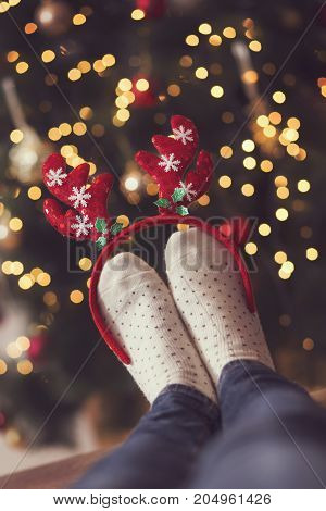 Detail of woman's feet wearing warm winter socks and small antlers placed on the table with nicely decorated Christmas tree and Christmas lights in the background. Selective focus on the antlers