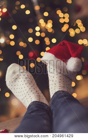 Detail of woman's feet wearing warm winter socks and small Santa's hat placed on the table with nicely decorated Christmas tree and Christmas lights in the background. Selective focus